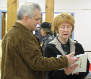 Project organizer Paul Hosford showing state senator Kate Sullivan a book of student designs.